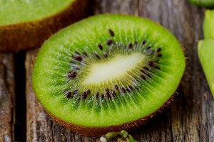 Sliced kiwi fruits on wooden table.