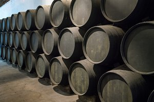 Row of stacked wooden wine barrels for sherry aging