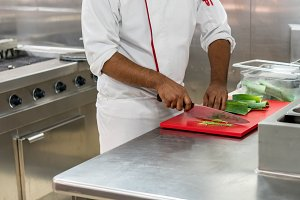 Chef preparing leeks in commercial kitchen