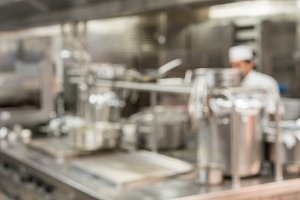 Defocused chef preparing food in commercial kitchen