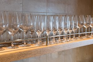 Row of different wine glasses on wooden shelf