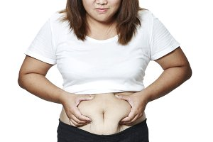 Portrait Asian woman's fingers measuring her belly fat