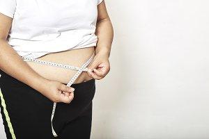Woman measuring her waistline