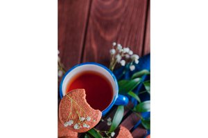 Close-up of a teacup with oatmeal cookies and spring gypsophila flowers on a warm wooden background. Blue ceramic cup on a blue linen napkin. Breakfast scene with copy space.