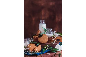 Homemade cookies with baking ingredients, a bottle of milk and an eggshell on a warm wooden background. Tasty homemade pastry concept with copy space. Spring baking photography.
