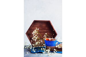 Blue ceramic teacup with a splash. Spring still life with a wooden tray and gypsophila flowers. Drink photography in high key.