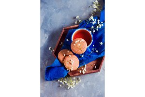 Oatmeal cookies, a small blue teacup and linen napkin on a wooden tray. Breakfast concept with homemade pastry and spring gypsophila flowers. Snack photo on a concrete background with copy space.