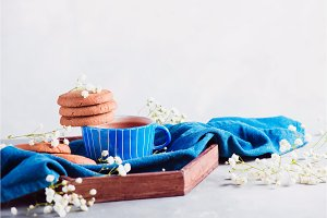 Cookies in a morning scene on a light background with copy space. Breakfast concept with homemade pastry and spring gypsophila flowers. Blue ceramic teacup on a wooden tray.