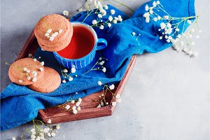 Header with oatmeal cookies, a small blue teacup and linen napkin. Breakfast concept with homemade pastry and spring gypsophila flowers. High key snack photo with copy space.