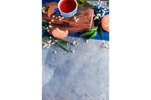 Teatime concept with homemade pastry and spring gypsophila flowers. Oatmeal cookies with wooden boxes on a concrete background with copy space.