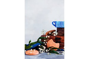 Cookies in a morning scene on a light background with copy space. Breakfast concept with homemade pastry and spring gypsophila flowers. Blue ceramic teacup with wooden boxes.
