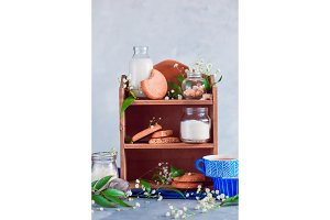 Kitchen shelf with baking ingredients for oatmeal cookies. Flour, milk and sugar on a light background with spring gypsophila flowers and green leaves. Cooking supplies with copy space.