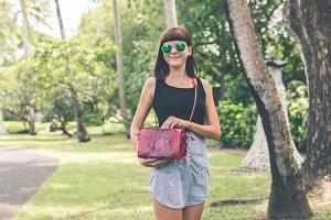 Fashionable woman with luxury snakeskin python handbag outside. Snakeskin fashion concept.