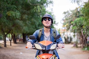 Young happy and handsome male motorcyclist in sunglasses and helmet riding on motorbike