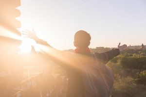 Young man raising hands up against sunlight - indicated success, achievement and victory