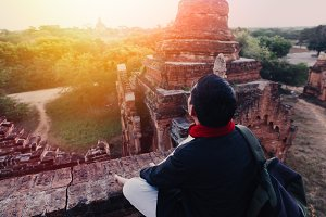 Silhouette of young male backpacker watching sunset and pagoda in Bagan, Burma