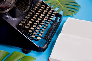 Open book with blank paper pages decorated with typewriter and leaves over bright blue background - with copy space