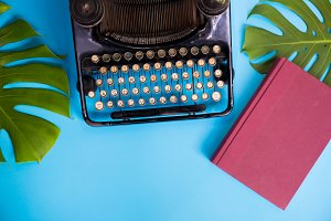 Old and vintage type writer machine and books and green leaves over blue background - with copy space