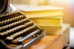 Old and vintage type writer machine and piles of books on wooden table - very selective focus