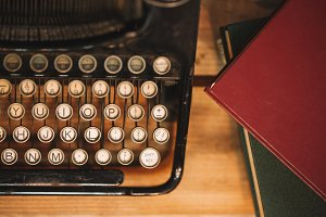 Old and vintage type writer machine and piles of books on wooden table - in vintage tone