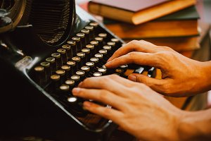 Human hands typing on vintage type writer machine and piles of books on wooden table - very selective focus
