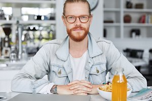 Confident redhaired male with beard and mustche spends free time at cafeteria, eats junk food, looks directrly into camera as sits at table with food, drink and modern portable laptop computer