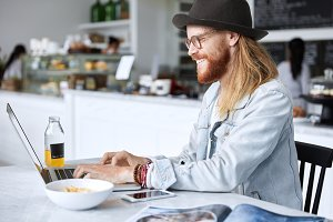 Shot of pleased bearded male in eyewear and hat, dressed in denim jacket, enjoys online communication with girlfriend, share news, keyboards text message, surrounded with modern devices and tasty dish