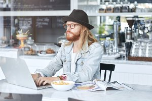 Serious concentrated bearded male model wears fashionable clothes sits at cozy cafe, comes to have lunch, being always connected and works remotely at laptop computer, uses free wireless internet