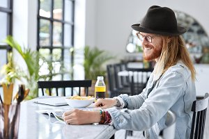 Stylish man with ginger beard and long hair sits at cafe during dinner break, examines intersting article in magazine, being at good mood. Male designer prepares for project, reads useful information