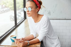 Thoughtful beautiful young female enjoys aroma cappuccino and online communication with friends on smart phone, looks pensively at window. Woman blogger thinks about creating personal website