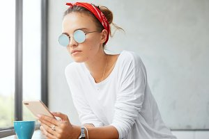 Portrait of female blogger in stylish outfit, reads some comments from followers on cell phone, views photos on web page, thinks of creating new video, has leisure time at home with cup of tea