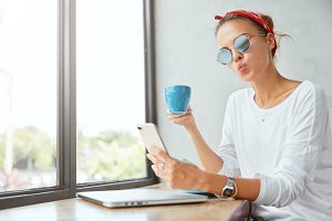 Shot of funny female model poses at camera of smart phone, makes grimace, holds mug with coffee. Beautiful woman uses modern gadgets for making photos, makes selfie. Youth and technolgy concept