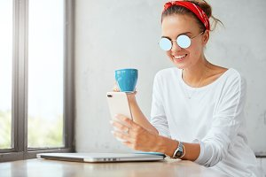 Smiling satisfied female student glad to finish creative task, shares good news on smart phone, happy to get job offer on email, drinks coffee. Young hipster girl enjoys online communication
