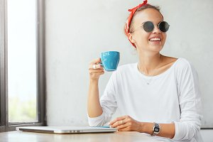 Indoor shot of glad smiling female in trendy eyewear, drinks tasty beverage, happy to spend free time with friends in cafeteria, gather together for creating project work. Relaxed beautiful woman