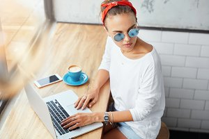 Successful female copywriter works remotely on modern laptop device, sits in coffee shop, thinks about something and works on text aditing, wears trendy shades, uses free internet connection.