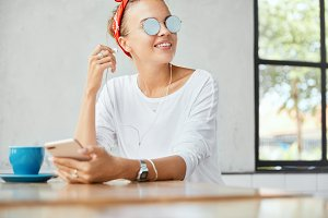 Cropped shot of fashionable young female in sunglasses, has cheerful expression, enjoys pleasant melody in earphones or listens online webinar, uses modern cell phone, sits at cozy cafe interior