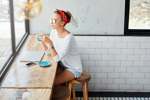 Attractive female model rests in coffee shop, wears sunglasses, jean shorts and white loose sweater, thinks about something while looks at window and drinks tasty hot coffee. People and leisure