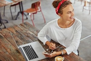 Beautiful young woman sits in front of opened laptop computer, holds mobile phone while listens audio files in playlist, drinks tasty coffee, looks happily aside, waits for friend. Technology concept