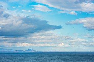 Seascape in blue tones. Cloudy sky.