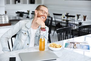 Relaxed cheerful bearded male designer has dinner break after creating project work, enjoys fresh orange juice and french fries, looks happily into distance, sits against spacious cafe interior