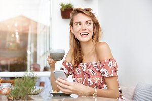 Adorable female model dressed casually, texts sms on mobile phone, drinks coffee, being happy to recieve good news, uses free internet connection at cafe. Happy young woman messages with friends