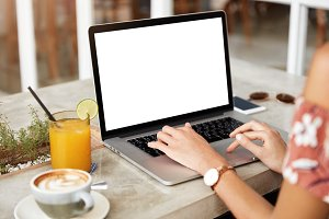 Cropped imgae of female employee types on keyboard of modern portable laptop computer with blank copy screen, sits at table with juice and cappuccino, works on financial report or checks email