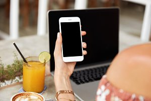 Close up of woman`s hands holds smart phone with blank copy space for your advertising content or promotional text, downloads updates, uses laptop compuer, drinks fresh orange juice and coffee