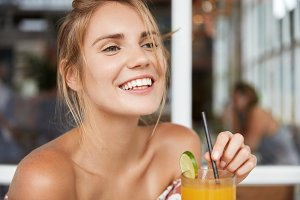 Close up shot of positive smiling young female enjoys martini cocktail in pub, discusses something with friends, laughs at good joke. Restful woman spends vacations abroad, poses with beverage