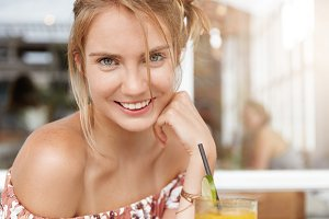 Close up shot of pleasant looking female model with shining broad smile, being in good mood, spends free time with boyfriend at cafeteria, drinks cold fresh beverage, looks happily at camera