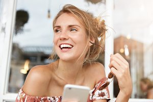 Happy hipster girl enjoys chatting with boyfriend on mobile phone, recieves nice compliments, being satisfied with high speed connection, holds shades, looks aside, has pleasant smile on face