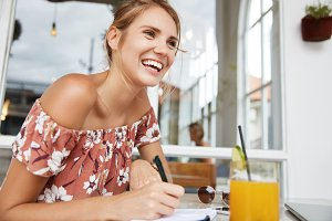 Positive female student sits at cafeteria, drinks tasty orange juice, writes notes, happy to pass one exam successfully, has summer session. Glad woman notes something in notepad, smiles pleasantly