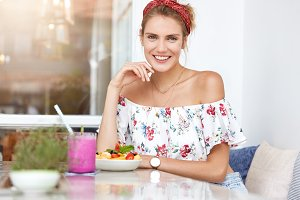 Attractive female model with pleasant smile, dressed in fashionable blouse, eats delicious fruit salad and drinks cocktail, enjoys free time at cafeteria, being in good mood. People, lifestyle, rest