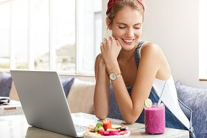 Relaxed pretty female blogger uploads multimedia files on laptop computer, looks with shy pleased expression down, drinks pink tasty shake and eats fruit salad. Satisfied woman does shopping online