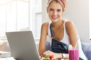 Beautiful young female in tank top and denim overalls, searches interesting ideas in internet for creating new article, uses free wireless connection, eats tasty fruit dessert, has charming warm smile